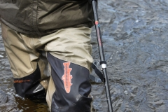 Fisherman wearing River-SENSE and using wading staff